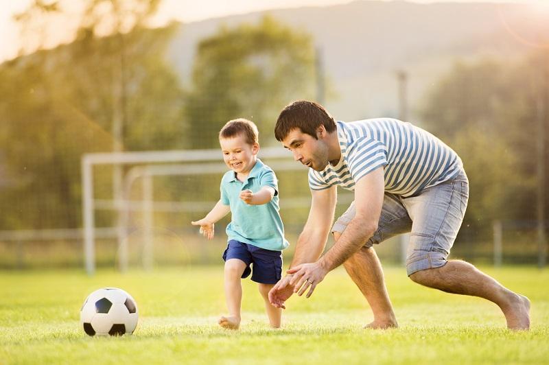 Папа и сын играют в футбол